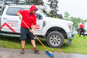 Professional roofer sweeping debris